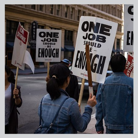 Union demonstrators march with signs saying one job should be enough